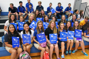 The freshmen show off their blue folders they were given on the first day.