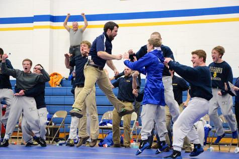 Wrestling Coach Joel Allen leaps into the air after freshman Blake Bradley pins his man and clinches the team's 35-32 win over Linn Mar.