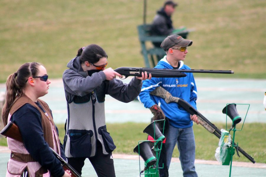 TAKING AIM After finishing her set of clay pigeons, Kylie Schueller, '19, watches her teammate, Macy Vance, '19, prepare for her next shot.