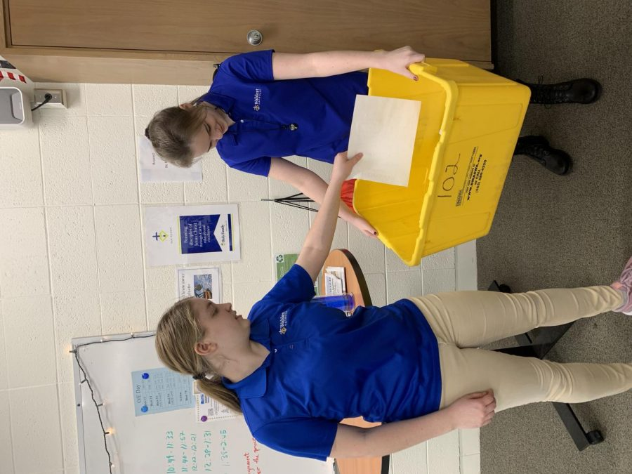 Veronica McDonald and Kylee Mitwede, '22, recycling in their classroom to prevent climate change.