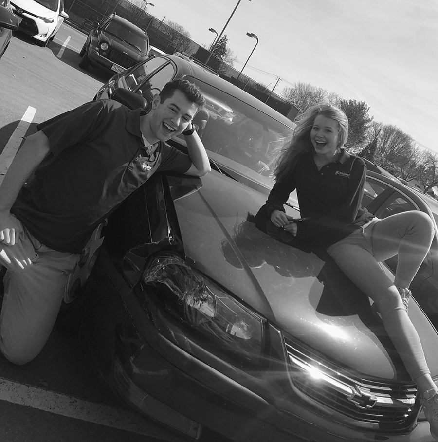 Tanner Rudiger and Klara Strand, '20, laugh while lounging on top of his car after school during the brief glimpse of summer weather.