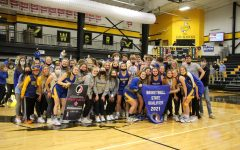 LOUD AND PROUD The Eagle's Nest joins the girls' basketball team as they pose with their state qualifier banner.