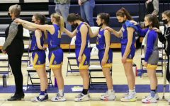 The girls' varsity basketball team stands at attention during the national anthem prior to the game against Xavier.