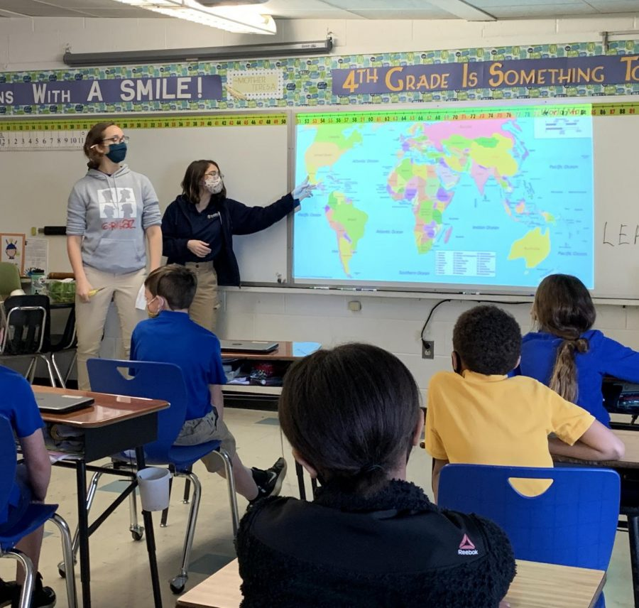 Kenna Wolbers and Leah Park, '23, teach elementary students at Resurrection how to lead a life of sustainability.